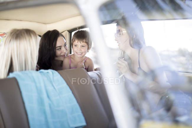 Freunde auf Roadtrip sitzen mit kleinem Mädchen im Auto — Stockfoto
