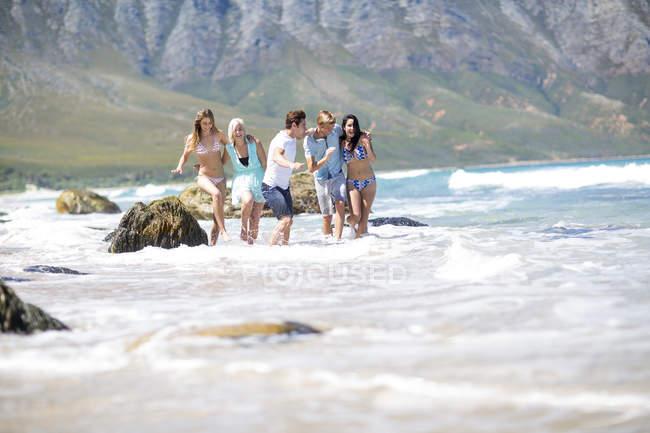 Amigos correndo juntos no mar — Fotografia de Stock