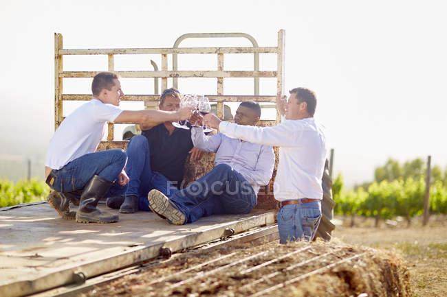 Wine growers tasting wine, sitting on trailer — Stock Photo