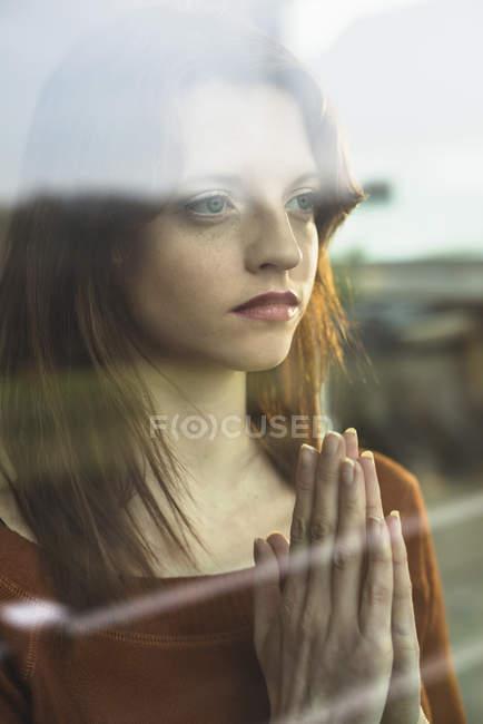 Ernste junge Frau mit Händen gefaltet hinter Fensterscheibe — Stockfoto
