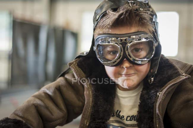 Garçon prétendant conduire vélomoteur vintage portant googles regardant caméra — Photo de stock