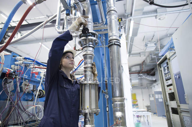 Technician in factory hall adjusting leveer at pipe — Stock Photo