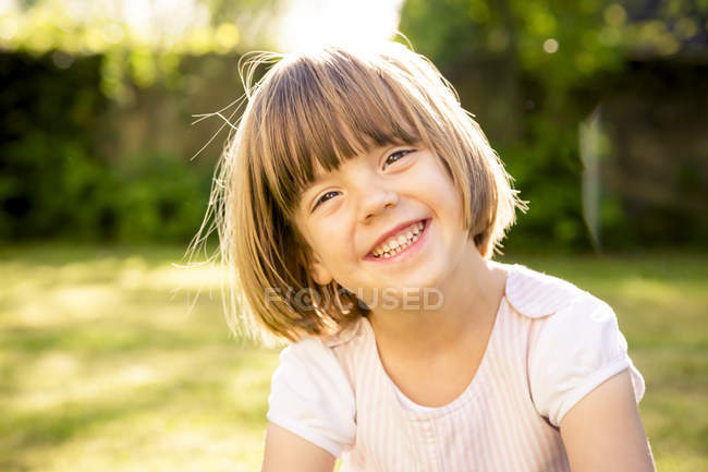 Portrait of smiling little girl in a garden — Stock Photo
