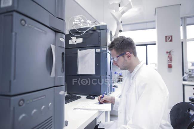 Scientifique en laboratoire microbiologique rédigeant un dossier — Photo de stock