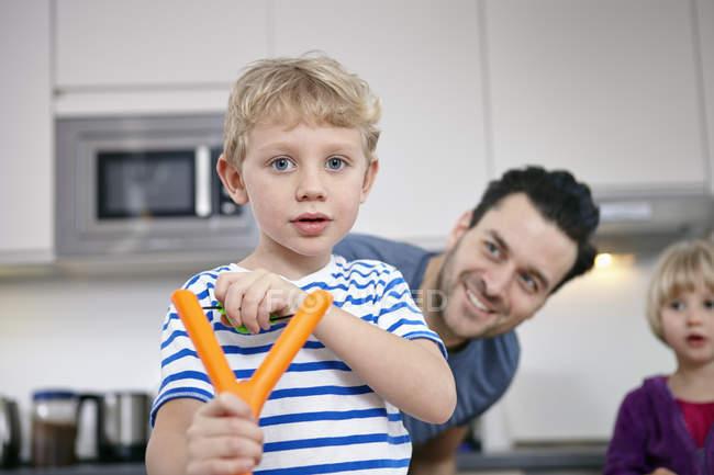 Маленький хлопчик кухні, навчитися використовувати рогатки — стокове фото