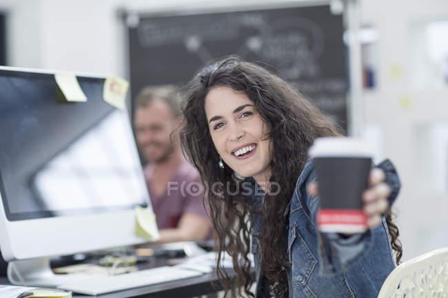 Creative office woman offering takeaway coffee — Stock Photo