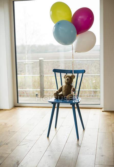 Ballons, Teddybär und Stuhl am Fenster — Stockfoto