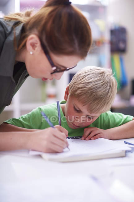 Nahaufnahme eines Lehrers, der Schüler beim Schreiben beobachtet — Stockfoto