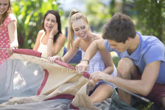Amigos felizes creación de una tienda de campaña juntos - foto de stock