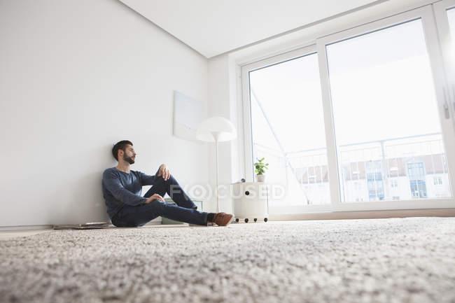 Jeune homme assis sur le sol du salon, regardant par la fenêtre — Photo de stock