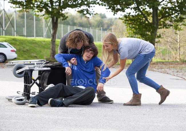 Двое молодых людей, оказание помощи молодым инвалидной коляске пользователь после падения — стоковое фото