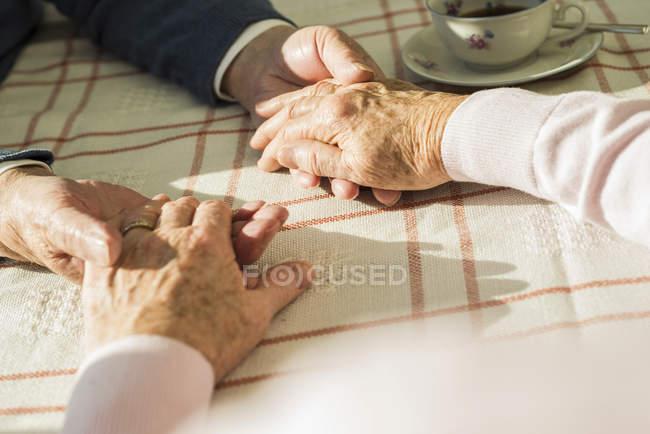 Senior couple holding hands — Stock Photo