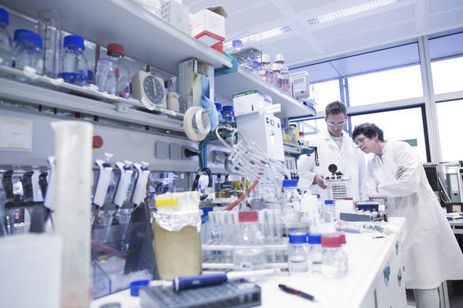 Scientists in microbiological lab discussing experiment — Stock Photo
