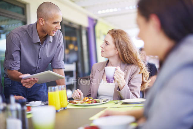 Businessman talking to colleague at dining table — Stock Photo
