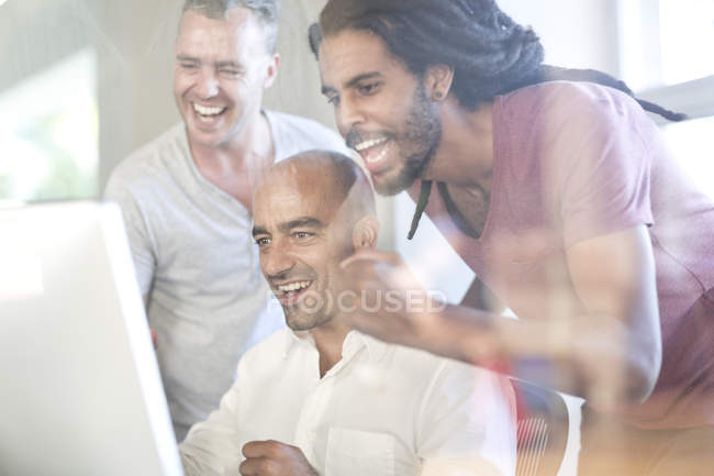 Three colleagues looking at computer screen in an office — Stock Photo