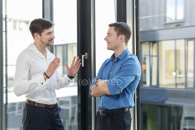 Two smiling businessmen communicating in office — Stock Photo
