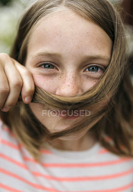 Portrait of smiling girl holding strand of hair under nose — Stock Photo