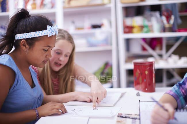 Due studentesse che discutono di dipinti in classe d'arte — Foto stock