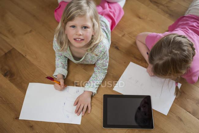 Duas irmãs com tablet digital e folhas de papel no chão — Fotografia de Stock