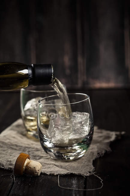 Pouring whisky into a tumbler with ice — Stock Photo