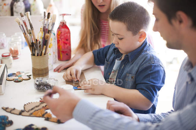 Boy tinkering in art class with classmate and teacher nearby — Stock Photo