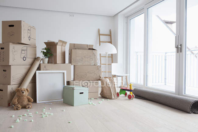 Cajas de cartón apiladas en interior plano - foto de stock