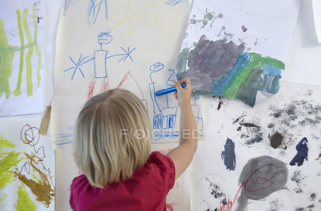 Petite fille peignant sur le mur de la chambre des enfants, vue arrière — Photo de stock
