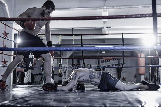 Boxer ausschlagen Gegner im Boxring — Stockfoto