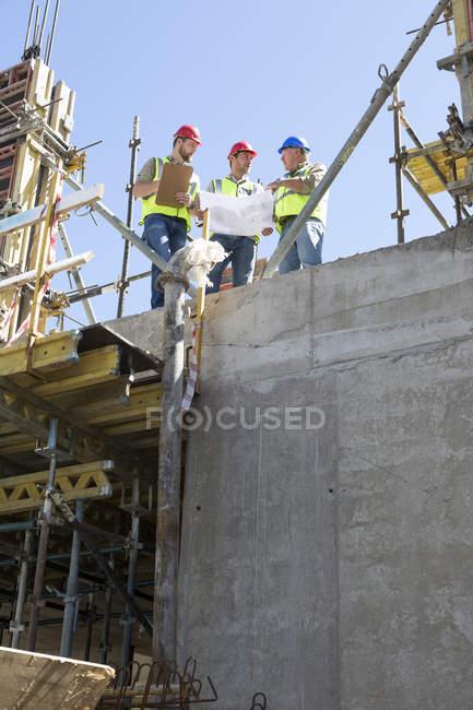 Lavoratori edili che discutono di piani edilizi in cantiere — Foto stock
