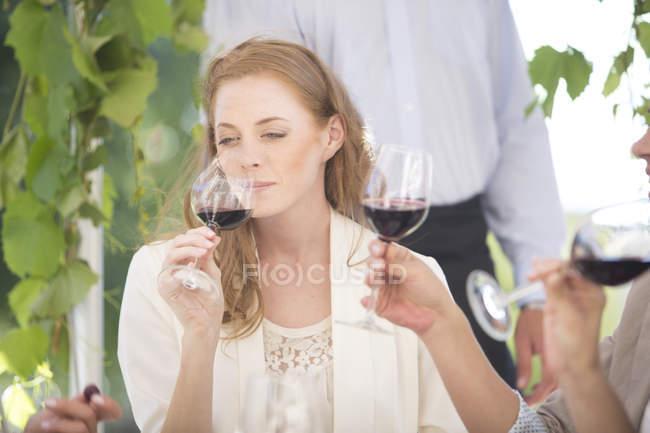 Женщина, пахнущий красное вино на дегустацию сессии — стоковое фото