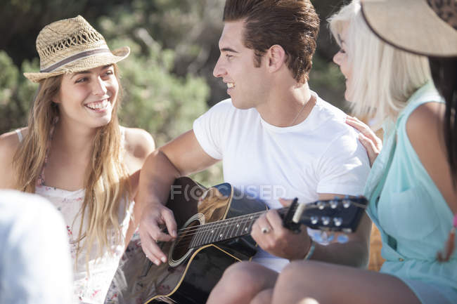Happy friends with guitar outdoors — Stock Photo