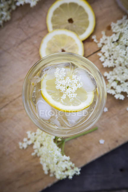 Glass of elderflower sirup with ice cubes and slices of lemon — Stock Photo