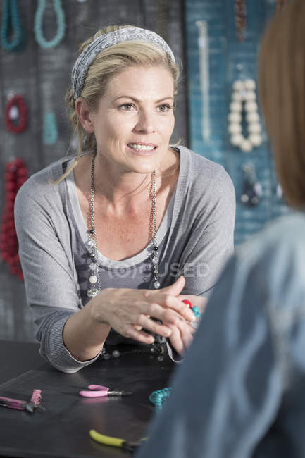 Woman showing beads to a customer — Stock Photo