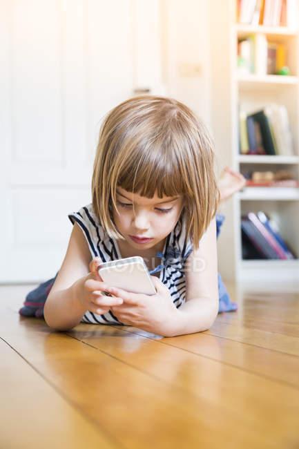 Niña acostada en el suelo de madera con teléfono inteligente - foto de stock