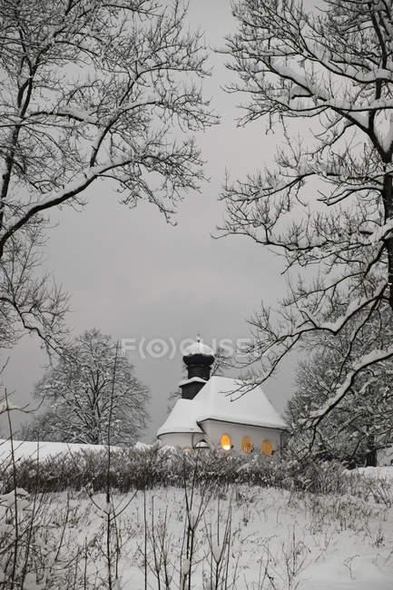 Германия, Кохель-ам-Зее, заснеженная протестантская церковь в сумерках — стоковое фото