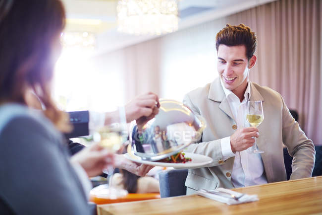Businessman looking at waiter lifting serving dome in hotel restaurant — Stock Photo