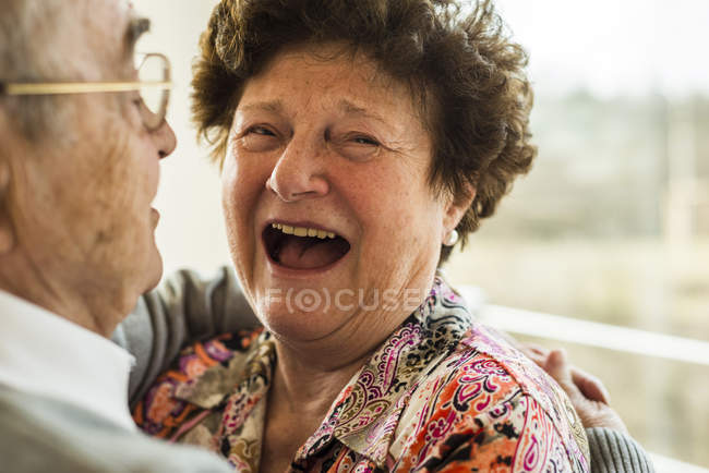 Laughing senior woman in the arms of her husband — Stock Photo