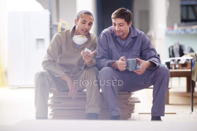 Carpinteros sentados en la pausa del café en taller - foto de stock