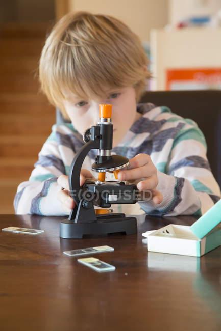 Mignon petit garçon avec microscope à la maison — Photo de stock