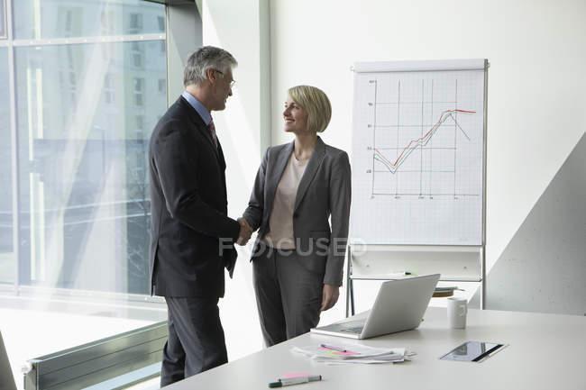 Бизнесмен и деловая женщина пожимают руки в конференц-зале — стоковое фото