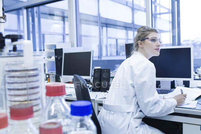 Biologiste travaillant en laboratoire au bureau — Photo de stock