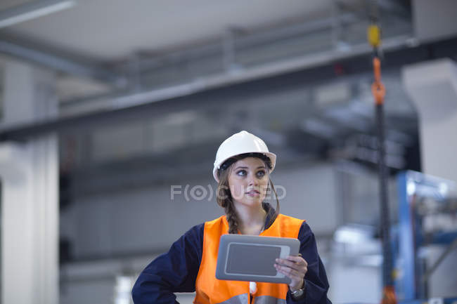 Technician with reflective vest in factory hall using digital tablet — Stock Photo