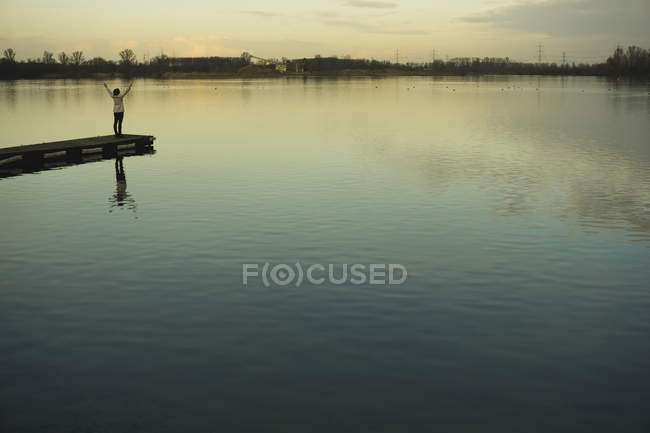 Germany, Roxheim, woman standing on wooden boardwalk at water — Stock Photo