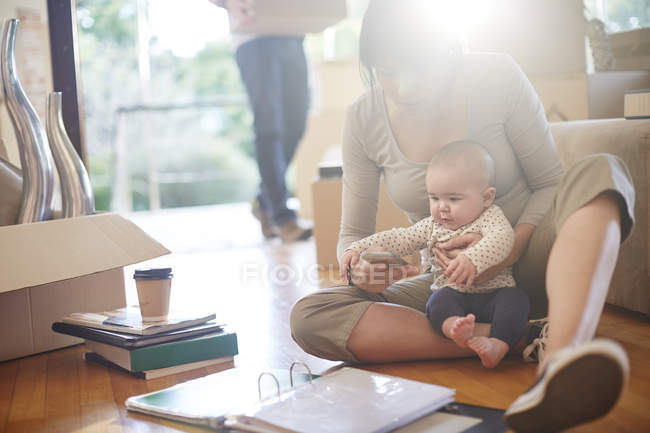 Family moving house, mother sitting with a baby — Stock Photo