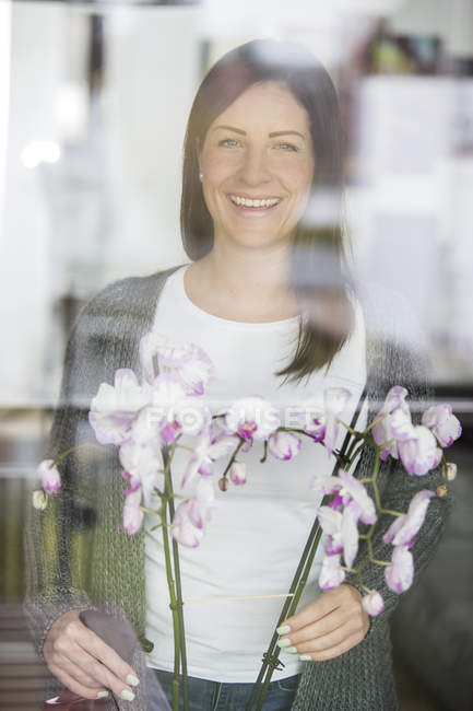 Woman with orchid looking through windowpane — Stock Photo