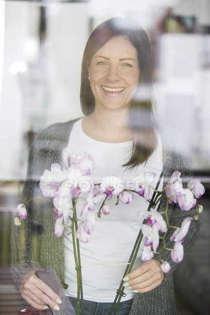 Frau mit Orchidee blickt durch Fensterscheibe — Stockfoto