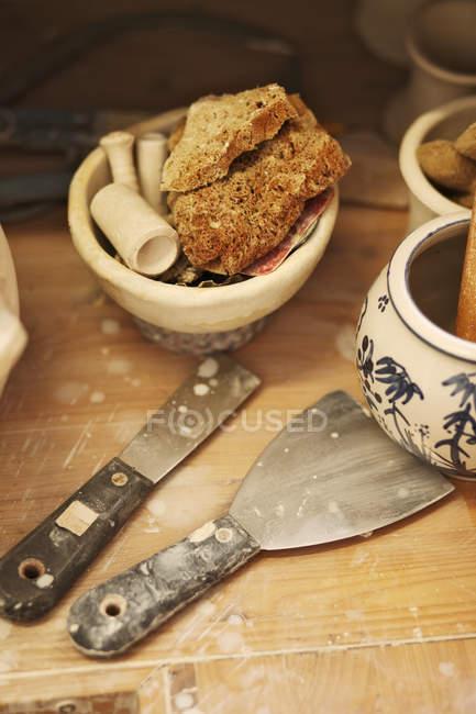 Werkzeuge in der Töpferwerkstatt über Holzoberfläche — Stockfoto