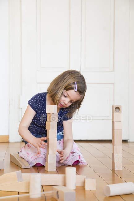 Маленька дівчинка, Скрадливий на поверсі, граючи з цегли Дерев'яне будинок — стокове фото