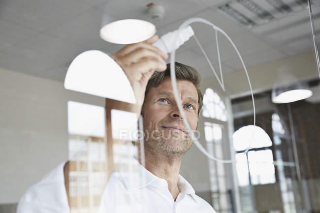 Homme d'affaires de dessin diagramme sur la vitre au bureau — Photo de stock