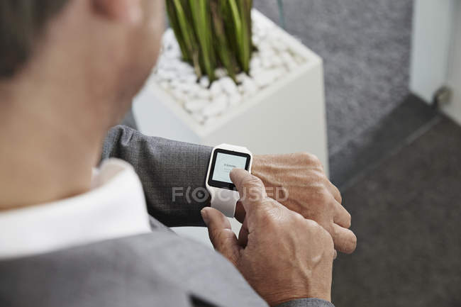 Businessman in office looking at smartwatch — Stock Photo